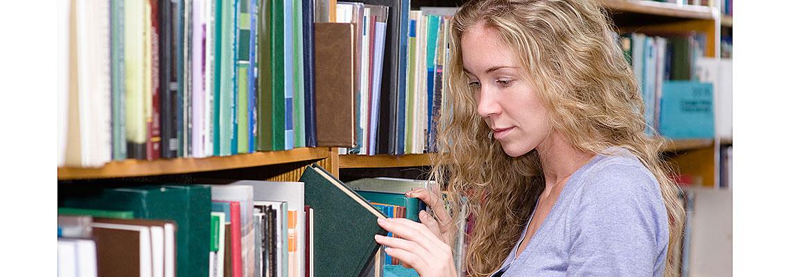 Nainen katsoo kirjaa.